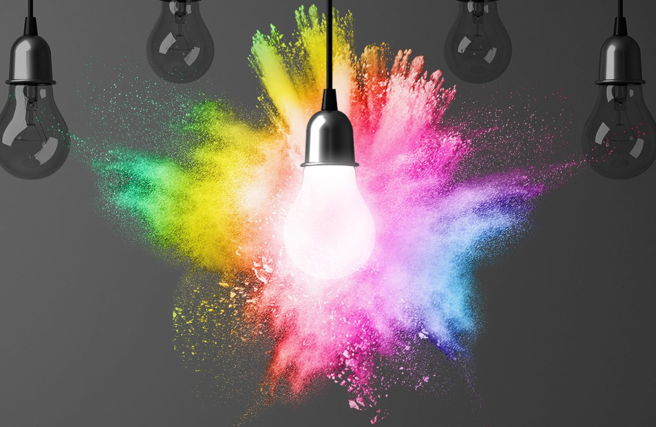 Lightbulb with explosion of colored powder in the background